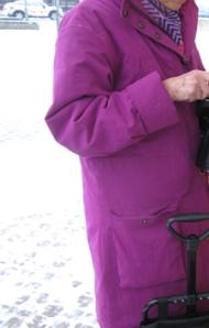 Dam i rödviolett kappa